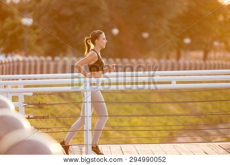 Beautiful Sporty Young Woman Running Over Bridge Early In Morning, Sunflare Effect, Empty Space