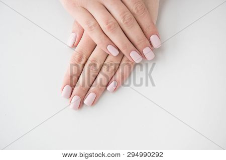 Manicured Hands On White Background. Hands With Manicured Nails Colored With Beige Nail Polish.