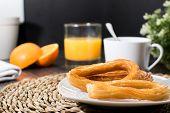 Tasty spanish churros, orange juice, coffee breakfast. Orange sliced. Tabletop with churros. poster