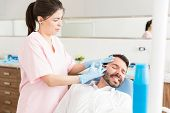 Irritated cosmetologist using botulinum toxin injection to treat man in skincare clinic poster