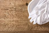 Disposable white plastic crockery on wooden background. Top view. Copyspace poster