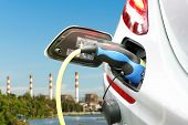plug of power cable electric supply during charging at ev car (electric vehicle charging) on electric power plant with smokestack and blue sky background poster