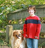 Young Boy Walking a Golden Retriever at the Park poster
