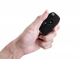 Man Hand Holding A Car Key Remote Isolated On White Background, Clipping Path