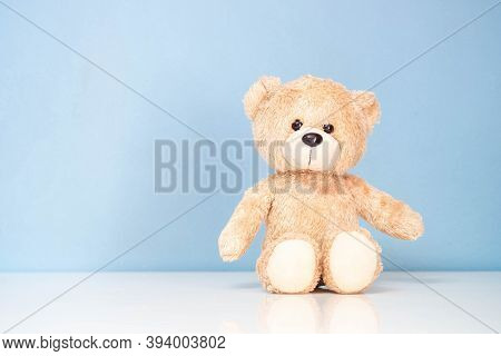 Teddy Bear Sitting On A White Table And Blue Background.
