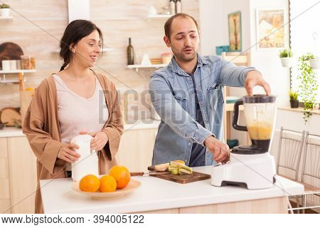 Couple Mixing Various Fruits For Nutritious And Healthy Smoothie. Healthy Carefree And Cheerful Life
