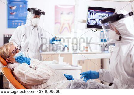 Senior Patient Presenting Teeth Pain Wearing Hazmat Suit Agains Coronavirus At Dentist. Elderly Woma
