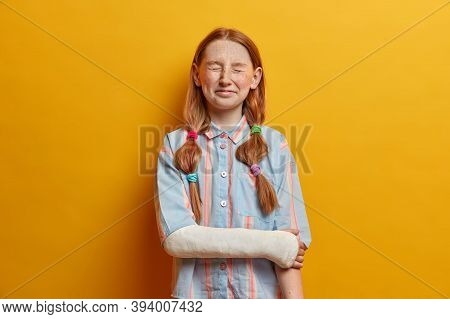 Portrait Of Overjoyed Little Girl Cannot Stop Laughing, Poses With Closed Eyes Has Ginger Hair Combe