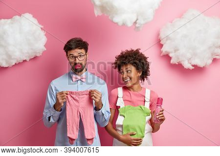 Married Mixed Race Couple Expect Baby, Buy Necessary Items For Newborn. Cheerful Pregnant Woman Hold