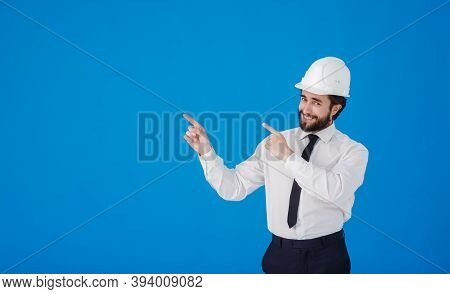 Handsome Man Industrial Engineer Wearing A White Hard Helmet And Pointing Finger Towards Something B