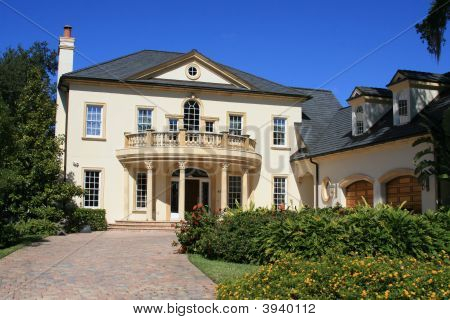 Mansion Home With Columns And Bright Blue Sky