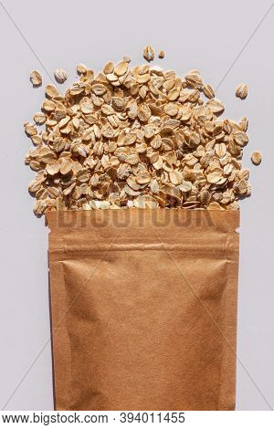 Brown Kraft Paper Pouch Bags With Oats Top View With Harsh Shadow White Background. Oatmeal Cereal P