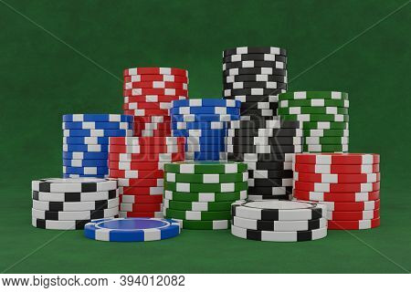 Stacked Poker Chips Isolated On Green Background. Black, Blue, Red, Green And White Casino Chips On
