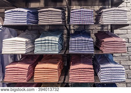 Clothes Displayed In Store, Mens Shirts Shirts Of Different Colors On The Shelf, Beautifully And Nea