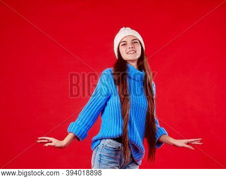 Beautiful Girl In A Sweater And A Hat On A Red Background.