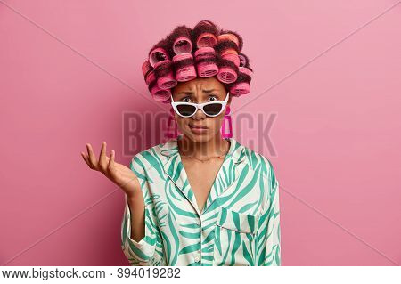 Displeased Indignant Woman Wears Curlers For Getting Hair Styled, Raises Hand And Puzzled By Unpleas