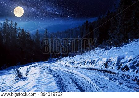 Carpathian Countryside On A Winter Night. Beautiful Mountainous Rural Landscape In Full Moon Light.
