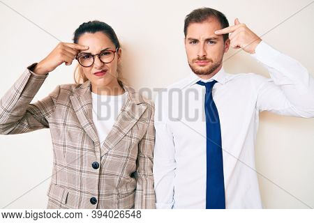 Beautiful couple wearing business clothes pointing unhappy to pimple on forehead, ugly infection of blackhead. acne and skin problem