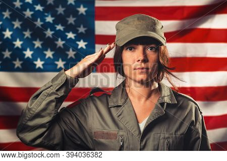 Veterans Day, Memorial Day, Independence Day. Portrat Of Female Soldier Saluting Against The Backgro