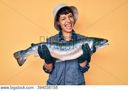 Beautiful brunettte fisher woman showing raw salmon winking looking at the camera with sexy expression, cheerful and happy face.