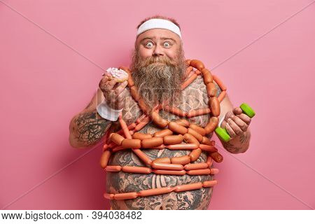 Obesity Causes. Funny Bearded Adult Man With Excess Weight, Struggles Against Sugar Addiction, Eats