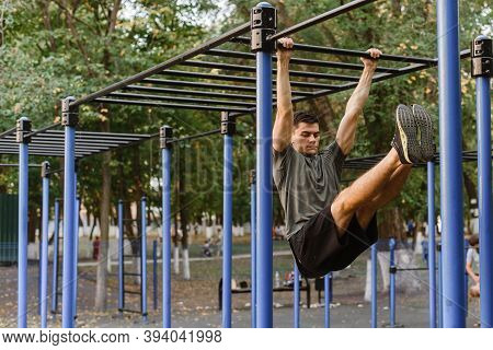 Shot Of A Young Man Doing Dips On The Uneven Bars. A Man Pulls Himself Up On A Horizontal Bar, Lifti