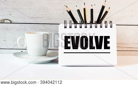 The Word Evolve Is Written In A White Notepad Near A White Cup Of Coffee On A Light Background