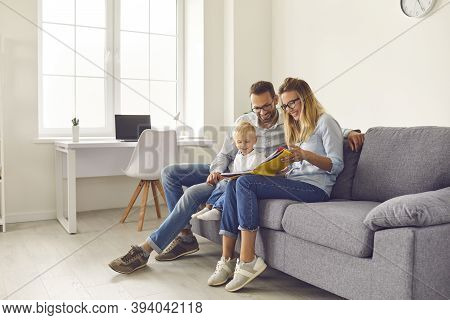 Happy Parents And Kid Sitting On Sofa, Reading Book Of Stories Or Looking Through Family Photo Album