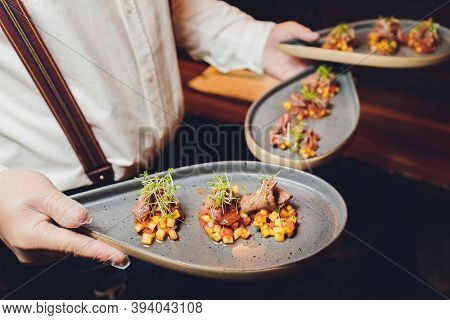 Snacks And Appetizers. Meat Cuts On A Wooden Plate With Horseradish And Croutons On A Black Table. F