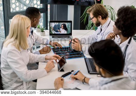 Team Of Multiracial Experienced Doctors Or Scientists, Having Video Conference With Their Young Conf