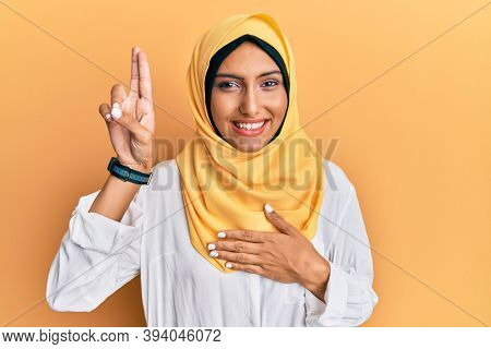 Young brunette arab woman wearing traditional islamic hijab scarf smiling swearing with hand on chest and fingers up, making a loyalty promise oath
