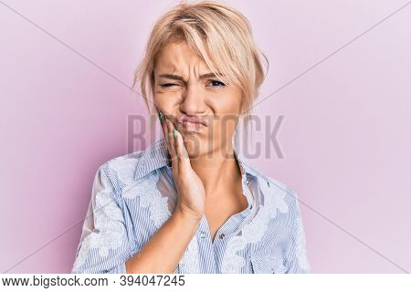 Young blonde girl wearing casual clothes touching mouth with hand with painful expression because of toothache or dental illness on teeth. dentist