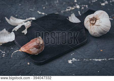 Still Life- Preparation Of The Sliced Garlic. On A Dark Background Lies The Husk Of Seasoning. The V