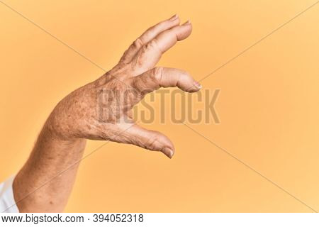 Senior caucasian hand over yellow isolated background picking and taking invisible thing, holding object with fingers showing space