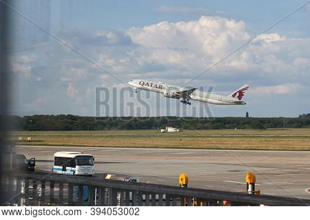 Budapest, Hungary - Circa 2020: Qatar airways Boeing 777-300 ER aircraft taking off at Budapest Liszt Ferenc Airport, view through the window glass of a terminal building. Delivery of medical supplies
