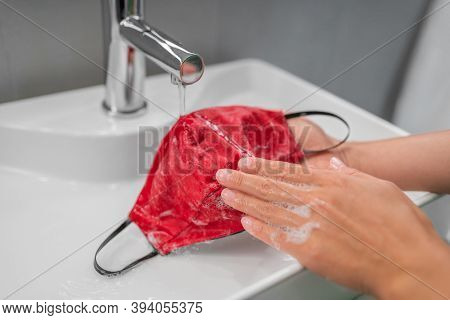 Washing cloth mask by hand after one use. Corona virus preventive face covering cleaning at home in sink.