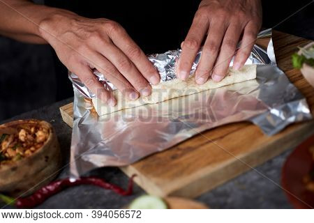 closeup of a young man wrapping in aluminum foil a durum or a burrito, filled with chicken meat cooked with different vegetables such as onion or red and green pepper