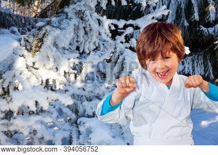 Winter coniferous forest. Huge spruce covered with snow. Handsome boy in white judo uniform training for judo. New Years is soon