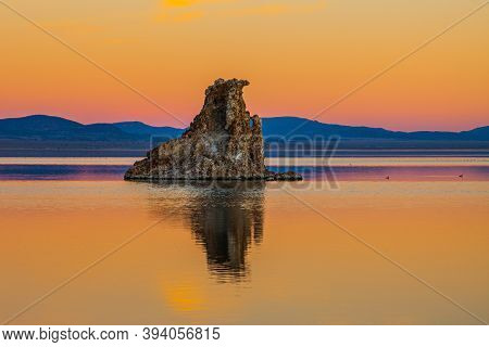 Magic sunset on the lake. Lime-tuff towers of bizarre shapes rise from the bottom of the lake. Magnificent reflections of tuff outliers in  water. Mono Lake is a salt lake in California.