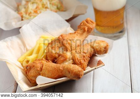 Fried chicken legs with French fries, cole slaw salad, and a glass of beer