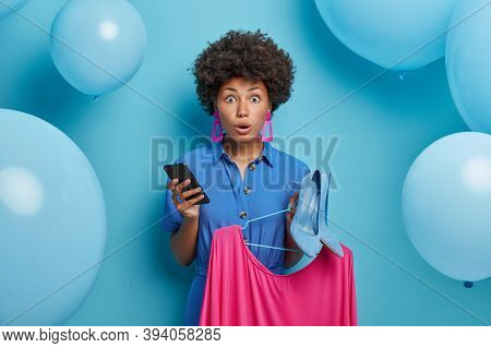 Emotive Scared Woman In Stylish Clothes, Chooses Dress And High Heel Shoes To Dress On Birthday Part