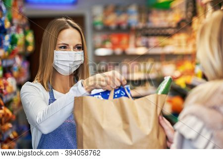 Adult woman in medical mask picking up order in grocery store