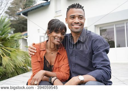 Portrait of happy mixed raced couple standing outside the house
