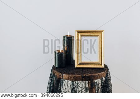 Golden picture frame on a spider lace tablecloth by black burning candles