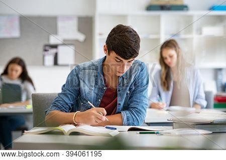 Focused young man taking notes from books for his study. College student sitting at desk and studying in high school library. Guy studying in classroom and completing project.