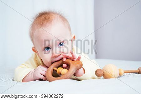 A Seven-month-old Girl With Blue Eyes Lies On Her Stomach In A Bright Room And Nibbles A Wooden Toy,