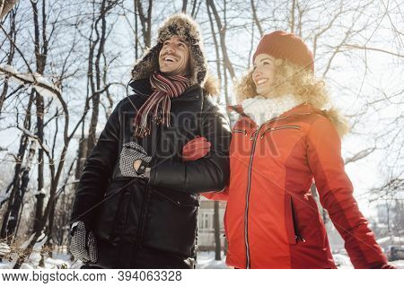 Couple having a walk through the woods in winter on a cold day