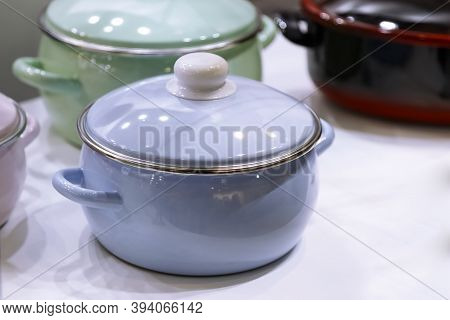 Many Enameled Steel Metal Multicolored New Modern Cooking Pots Enamelware Stand On A Shelf In The Ki