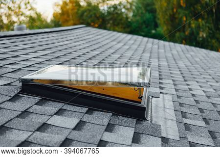 new open roof window on shingles flat polymeric roof-tiles