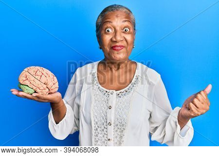Senior african american woman holding brain screaming proud, celebrating victory and success very excited with raised arm